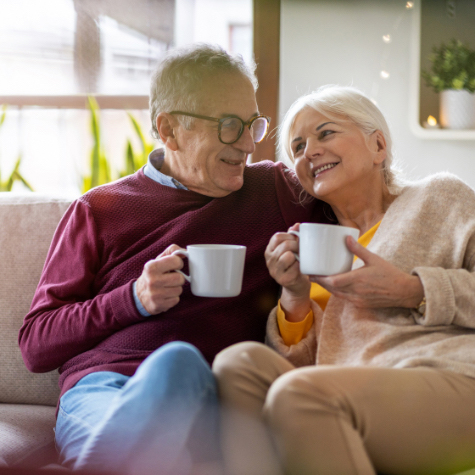 an elderly couple snuggled up on the couch drinking coffee