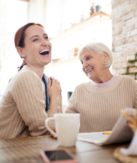 A young woman with coffee laughing while sitting next to an elderly woman who is smiling and looking at her.