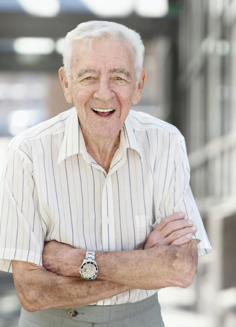 an elderly man standing with his arms cross and smiling