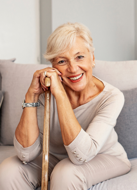 an elderly woman sitting on a couch smiling